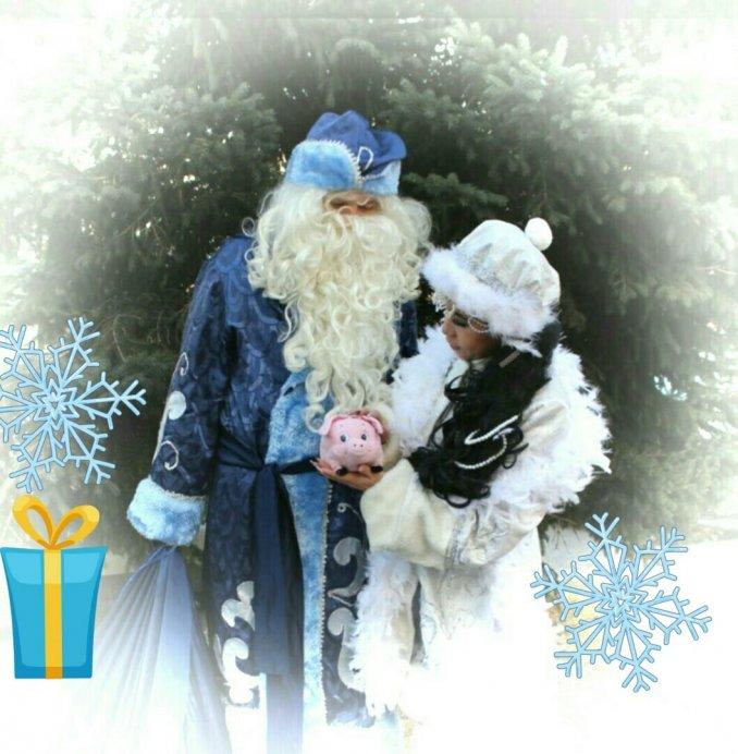 Дед Мороз и Снегурочка, с очаровательным символом года, приносящим удачу, всем, кто потрет левую ладонь о его пяточек